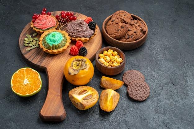 Vista frontal deliciosos bolos com biscoitos e frutas em fundo escuro