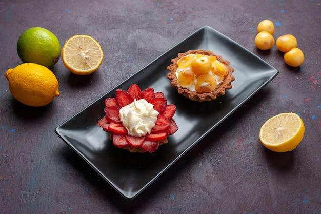 Vista frontal deliciosos bolos cremosos dentro do prato com limões frescos na superfície escura