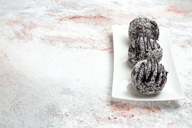 Vista frontal deliciosos bolos de chocolate com glacê na superfície clara - biscoito com açúcar de chocolate bolo doce assar biscoito