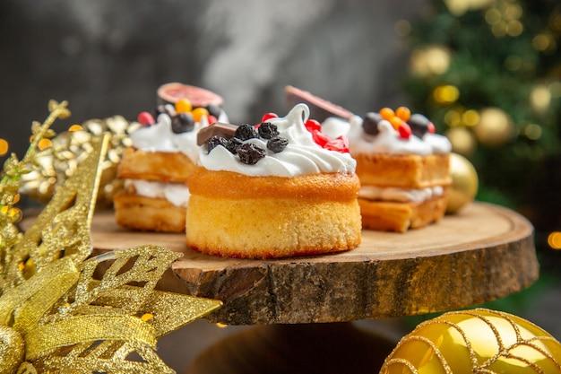 Vista frontal deliciosos bolos de creme ao redor da árvore de ano novo, brinquedos na mesa escura, sobremesa, bolo, doce, foto, creme