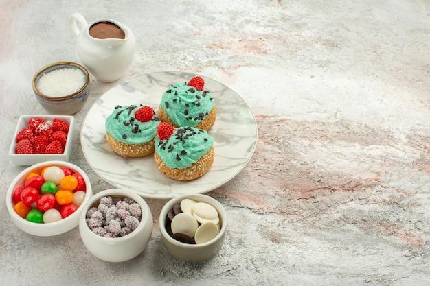 Vista frontal deliciosos bolos de creme com doces coloridos e biscoitos no fundo branco.