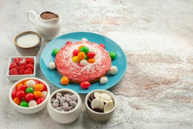 Vista frontal deliciosos bolos de creme com doces coloridos sobre fundo branco claro.