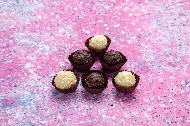 Vista frontal deliciosos bombons de chocolate branco e chocolate escuro sobre fundo rosa.