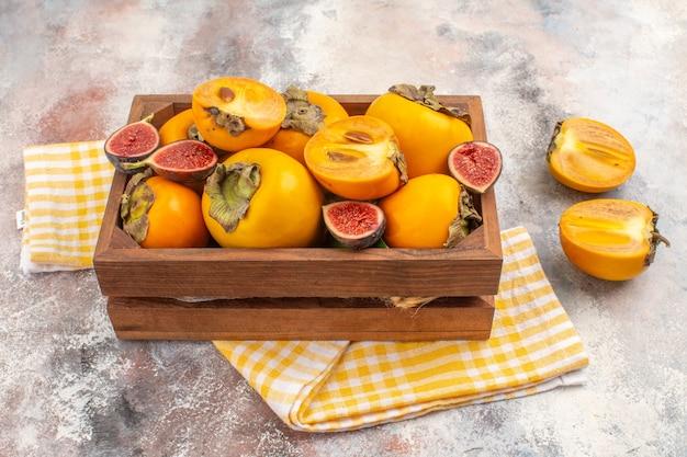 Vista frontal deliciosos caquis e figos cortados em uma caixa de madeira toalha de cozinha amarela em fundo nude