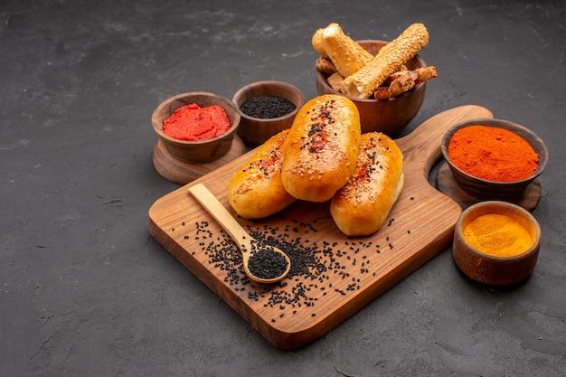 Vista frontal deliciosos hambúrgueres recém-saídos do forno com diferentes temperos em fundo cinza torta de carne bolo assado no forno