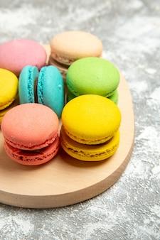 Vista frontal deliciosos macarons franceses bolos coloridos na mesa branca torta de bolo de açúcar biscoito doce