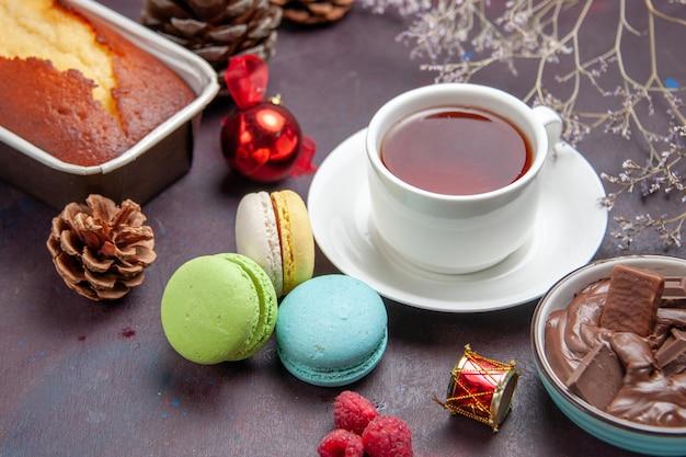 Vista frontal deliciosos macarons franceses com chocolate e uma xícara de chá no fundo escuro chá bebida torta biscoito bolo biscoito