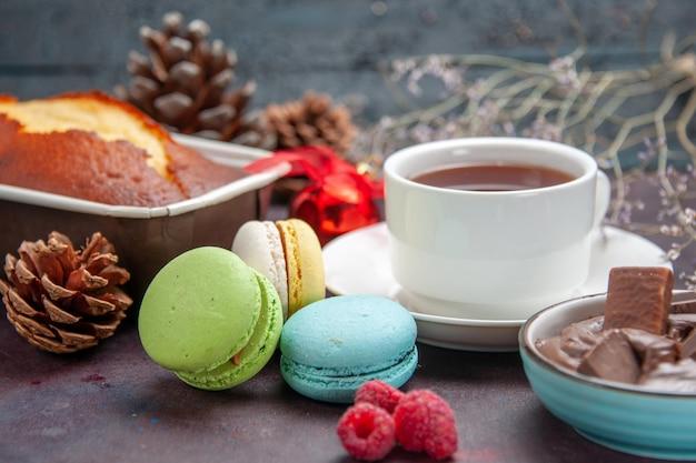 Vista frontal deliciosos macarons franceses com chocolate e uma xícara de chá no fundo escuro, chá, bebida, torta, biscoito, bolo, biscoitos