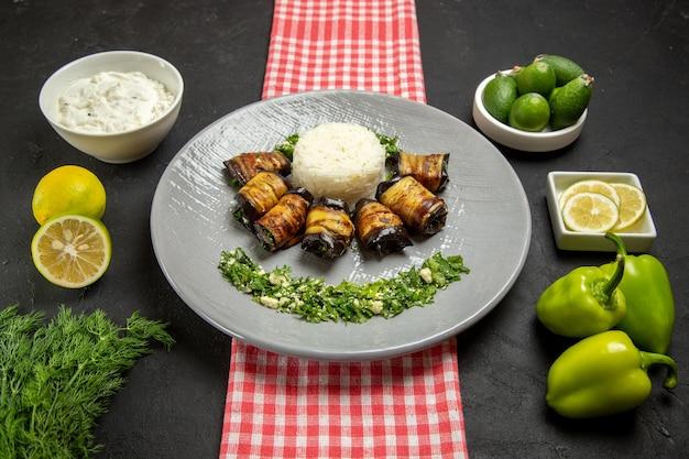 Vista frontal deliciosos pãezinhos de berinjela, prato cozido com arroz e ingredientes diferentes na superfície escura.