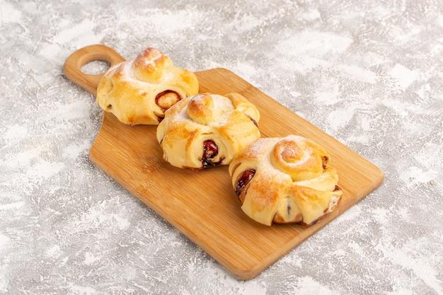 Vista frontal deliciosos pastéis de frutas doces assados na superfície cinza bolo pastelaria doce chá