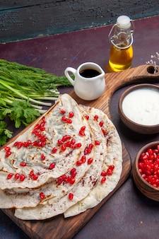 Vista frontal deliciosos qutabs pitas com carne moída dentro e com romãs frescas em massa de superfície escura com farinha de carne de pita