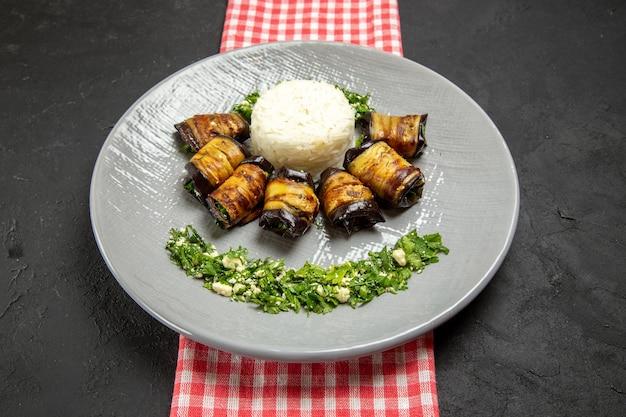 Vista frontal deliciosos rolos de berinjela prato cozido com arroz na superfície escura cozinhando arroz vegetal comida