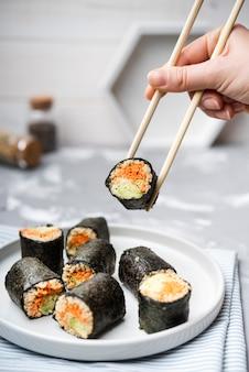 Vista frontal deliciosos rolos de sushi e fundo desfocado
