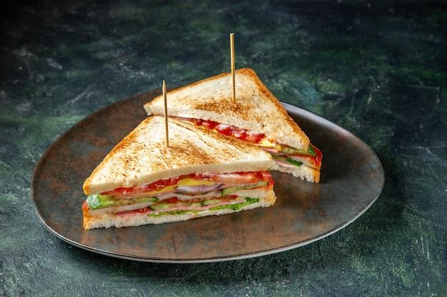 Vista frontal deliciosos sanduíches de presunto dentro da superfície escura do prato