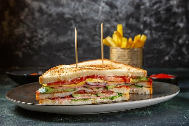 Vista frontal deliciosos sanduíches de presunto dentro do prato com superfície escura de batata frita