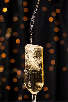 Vista frontal, derramando champanhe no copo