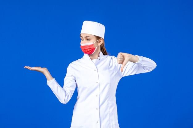 Vista frontal descontente jovem enfermeira em traje médico com máscara protetora vermelha sobre azul