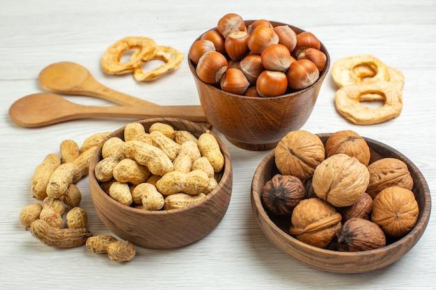 Vista frontal diferentes nozes, amendoins, avelãs e nozes na superfície branca