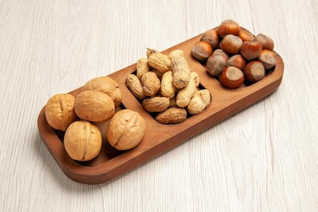 Vista frontal diferentes nozes frescas amendoim, avelãs e nozes na mesa branca, porca lanche muitas plantas