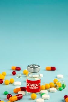 Vista frontal diferentes pílulas coloridas com vacina na superfície azul cor do laboratório saúde covid- hospital ciência pandemia droga