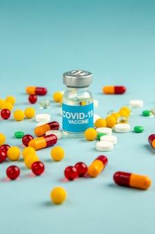 Vista frontal diferentes pílulas coloridas com vacina na superfície azul laboratório saúde covid- hospital vírus ciência pandemia drogas cores