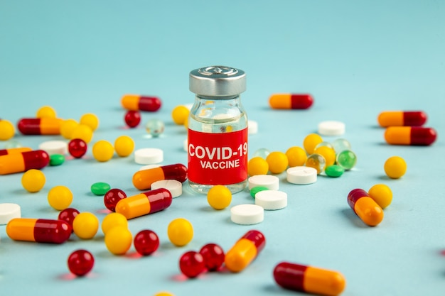 Vista frontal diferentes pílulas coloridas na superfície azul cor do laboratório covid- hospital vírus ciência pandemia droga