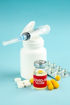 Vista frontal diferentes pílulas com injeção e vacina em fundo azul