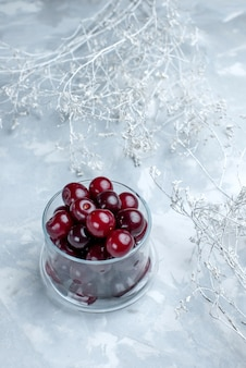 Vista frontal distante de cerejas ácidas frescas dentro de um pequeno copo de vidro na mesa branca
