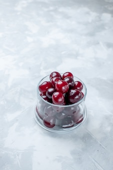 Vista frontal distante de cerejas ácidas frescas dentro de um pequeno copo de vidro na mesa com luz branca