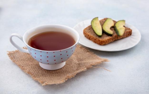 Vista frontal do abacate fatiado saudável em uma lâmina de pão em um prato branco com uma xícara de chá no pano de saco na superfície branca