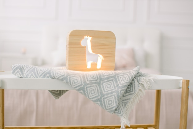 Vista frontal do abajur de madeira com girafa corta a imagem, no cobertor cinza no interior aconchegante do quarto claro.