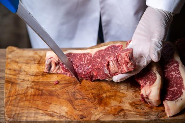 Vista frontal do açougueiro cortar carne em luvas brancas, segurando uma faca grande na mesa de madeira