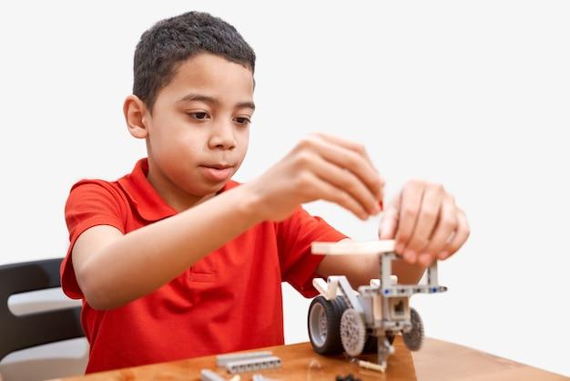 Vista frontal do adorável menino africano conentrado sentado à mesa e usando o kit de construção para crianças
