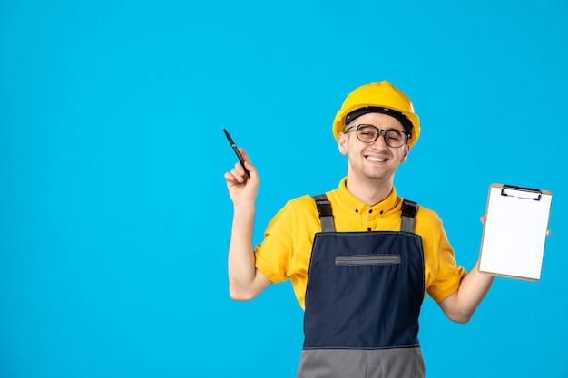Vista frontal do alegre construtor masculino de uniforme com uma nota de arquivo nas mãos na parede azul