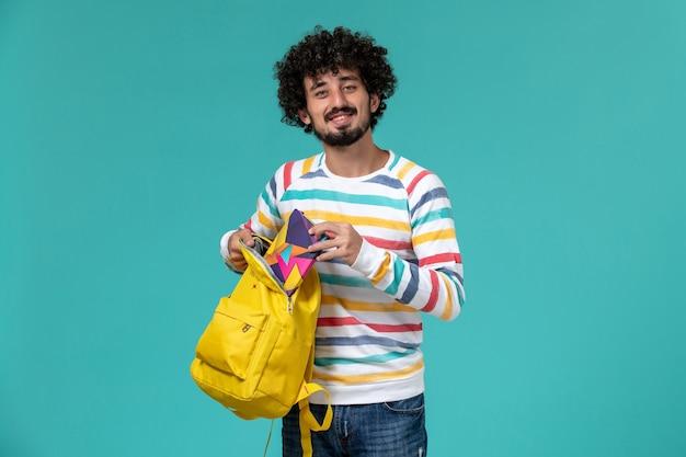 Vista frontal do aluno segurando uma mochila amarela e um caderno na parede azul