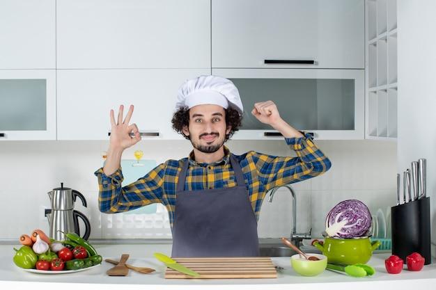 Vista frontal do ambicioso chef masculino com legumes frescos e cozinhando com utensílios de cozinha e fazendo gesto de óculos mostrando sua musculatura na cozinha branca
