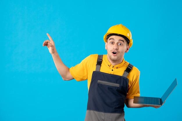 Vista frontal do animado trabalhador masculino de uniforme com laptop na superfície azul