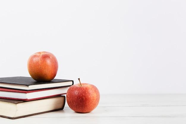 Vista frontal do arranjo de livro e maçãs
