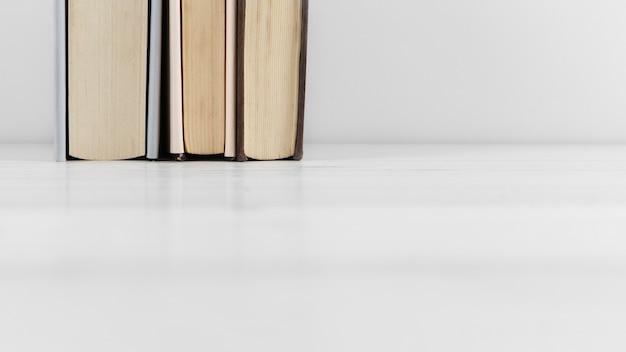 Vista frontal do arranjo de livros no fundo liso