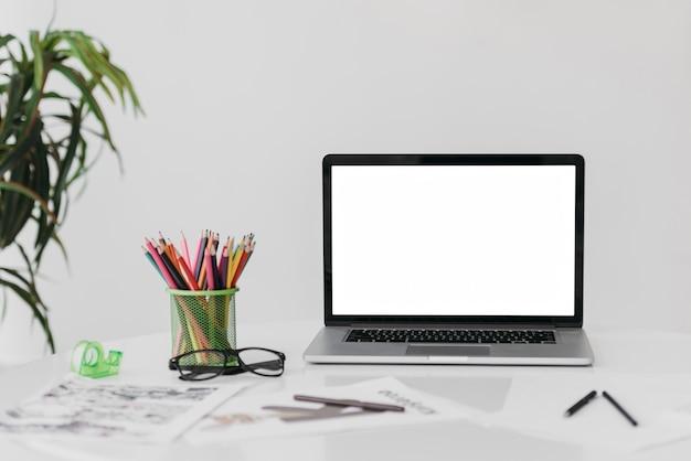 Vista frontal do arranjo moderno da mesa de escritório com laptop