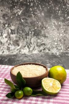 Vista frontal do arroz cru com limões na superfície escura de alimentos crus, cor de frutas
