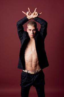 Vista frontal do artista masculino posando de terno sem camisa e blazer aberto