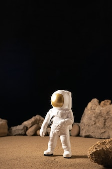 Vista frontal do astronauta branco ao redor de pedras no preto