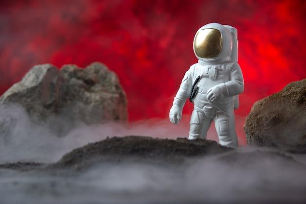 Vista frontal do astronauta branco com pedras na lua fantasia vermelha sci fi cósmica