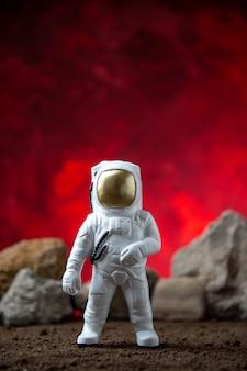 Vista frontal do astronauta branco com pedras na lua, superfície vermelha, sci fi fantasy cósmico