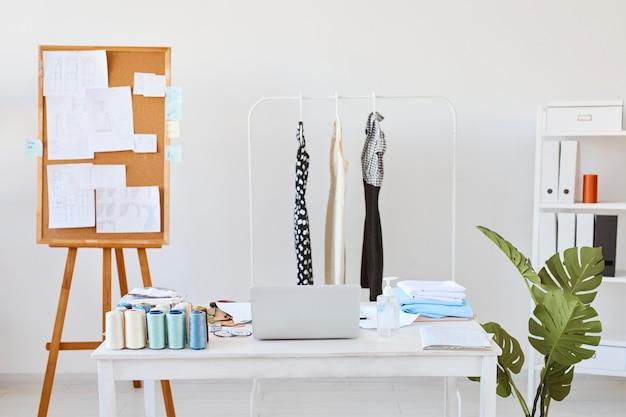Vista frontal do ateliê de moda com quadro de ideias e mesa com linha de roupas
