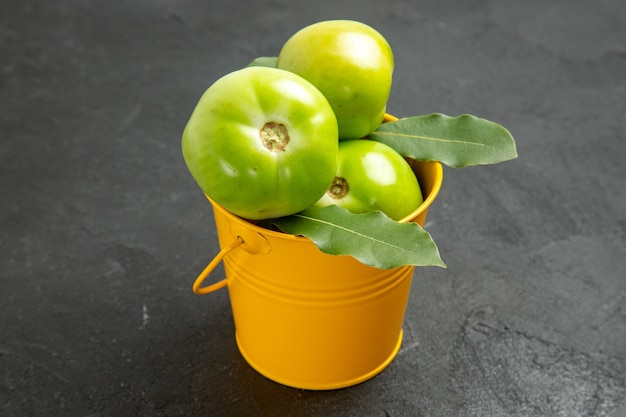 Vista frontal do balde de tomates verdes e folhas de louro em fundo escuro