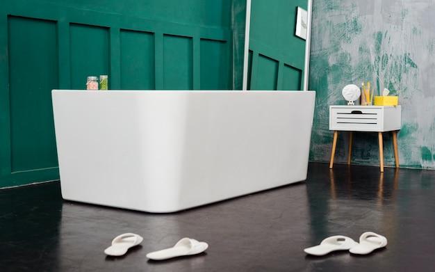 Vista frontal do banheiro com espelho e chinelos