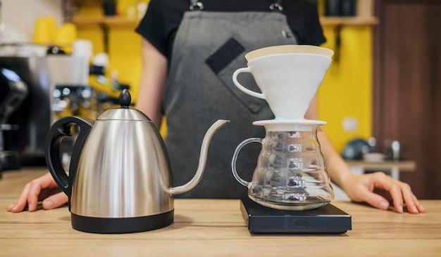 Vista frontal do barista com filtro de café e chaleira