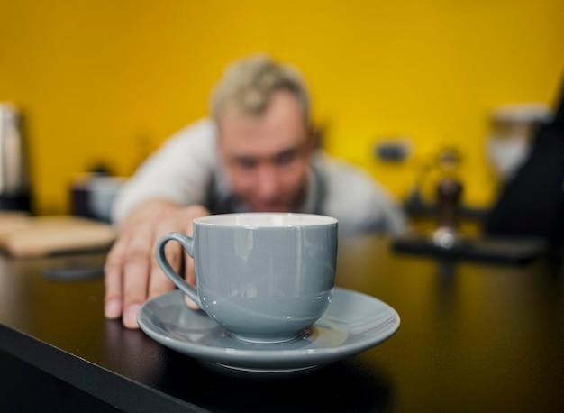 Vista frontal do barista desfocado, olhando para a xícara de café